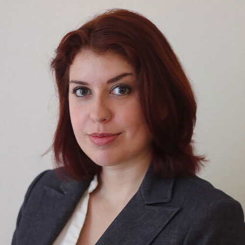 Nora Jacobsen Ben Hammed headshot wearing a dark suit jacket and white shirt.